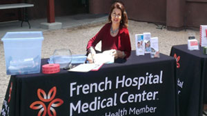 Mara Purl signs copies of her novels that were presented as gifts from French Hospital to guests at the event.